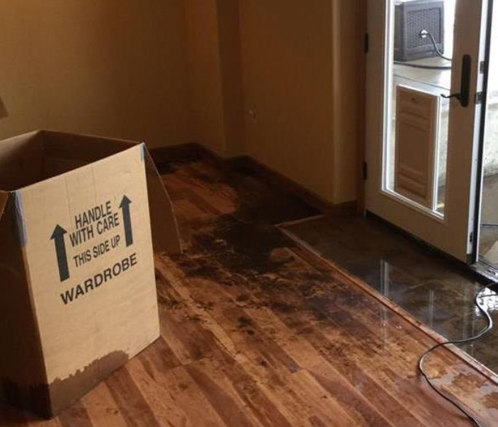 water damaged hardwood.  Water still on floor. Box in middle of floor.